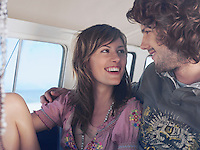 Young couple in camper van smiling at each other