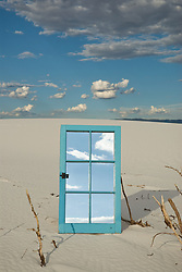 Mirrored window frame reflecting the sky and clouds on white sand dune in Whites Sands National Park, NM