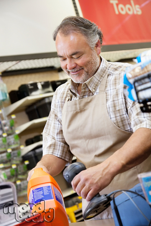 Happy mature salesperson using barcode reader at checkout counter in hardware counter