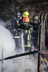 Calais, France. 04/03/16. Fire crews put out the smouldering remains of a shelter that was set on fire in the Calais 'Jungle'. French authorities are clearing the southern half of the Calais 'Jungle' camp, which charities estimate to contain 3,500 people.