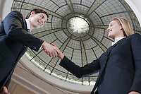 Businessman and businesswoman shaking hands under dome low angle view