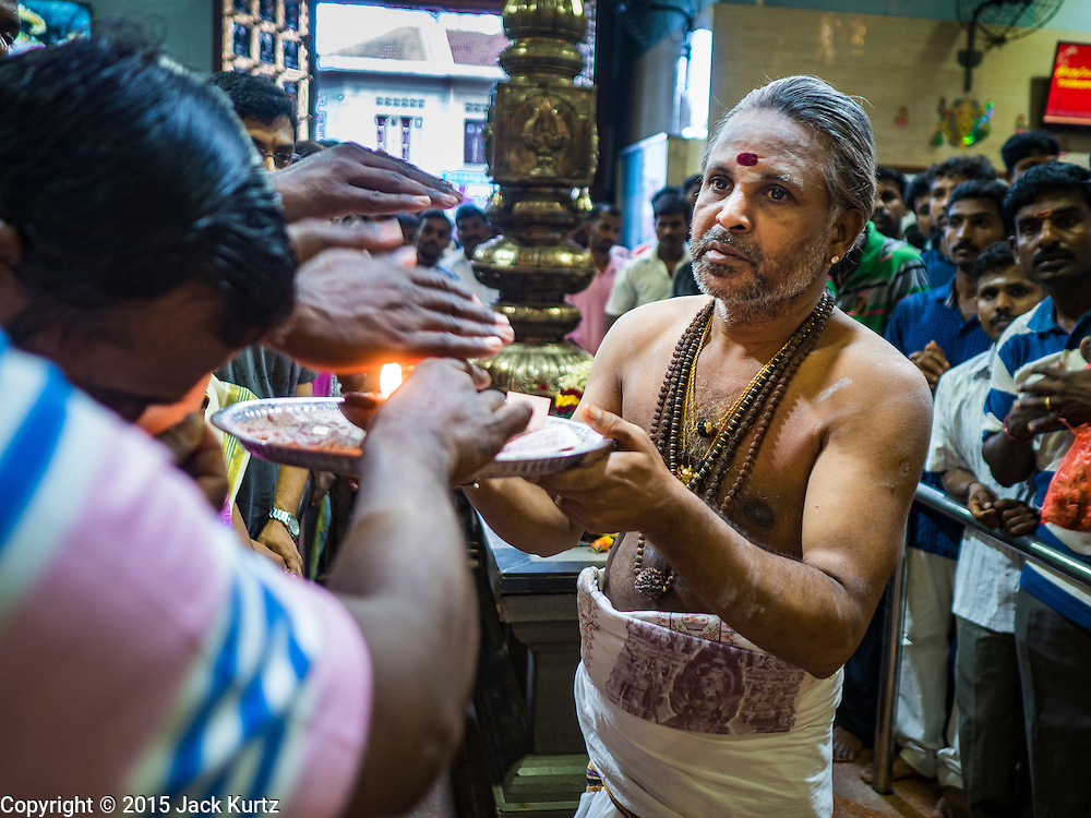 """27 DECEMBER 2015 - SINGAPORE, SINGAPORE:  A Hindu priest participates in services at Sri Veeramakaliamman Temple in Singapore. Sri Veeramakaliamman Temple in the """"Little India"""" section of Singapore, was one of the first Hindu temples in Singapore and is dedicated to the Goddess Kali, the Hindu """"Destroyer of Evil.""""  It's on Serangoon Road, which at one time was the center of Singapore's Indian community and served Indian immigrants who worked in the cattle trade that was based around Serangoon Road in the 19th century. Now the temple is a popular tourist site.     PHOTO BY JACK KURTZ"""