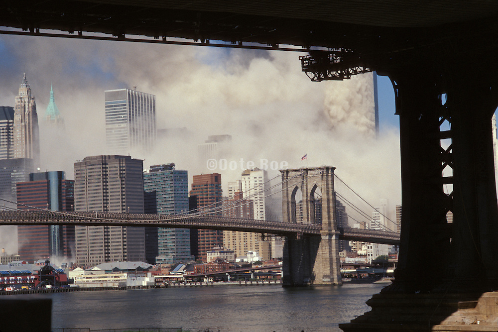 September 11 2001 World Trade Center first tower collapsing. Manhattan Bridge pillar in the foreground.