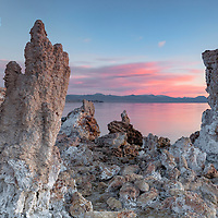 Early morning light on clouds framed by tufas and reflecting in the calm waters of Mono Lake. Lee Vining, California