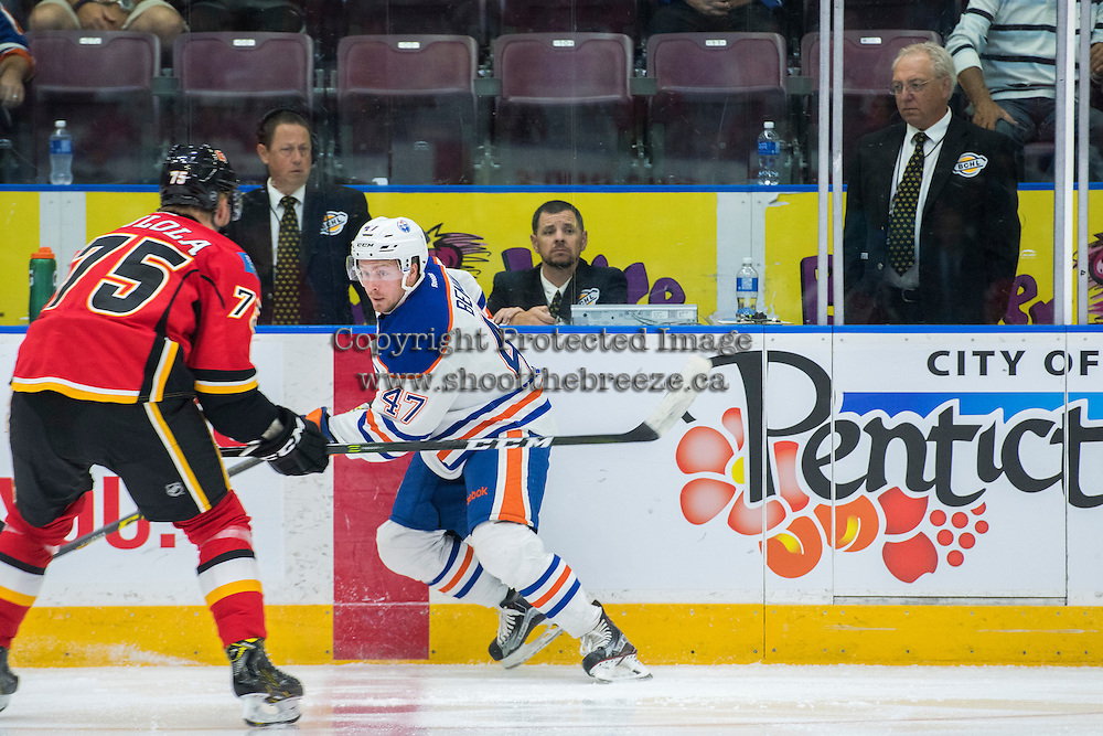 PENTICTON, CANADA - SEPTEMBER 17: Eetu Tuulola #75 of Calgary Flames skates for the check against Joey Benik #47 of Edmonton Oilers on September 17, 2016 at the South Okanagan Event Centre in Penticton, British Columbia, Canada.  (Photo by Marissa Baecker/Shoot the Breeze)  *** Local Caption *** Eetu Tuulola; Joey Benik;