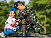 "14 JANUARY 2017 - BANGKOK, THAILAND: A Thai soldier helps a child look at a FN MAG machine gun mounted on a HUMVEE during Children's Day activities at the King's Guard, 2nd Cavalry Division base in Bangkok. Thailand National Children's Day is celebrated on the second Saturday in January. Known as ""Wan Dek"" in Thailand, Children's Day is celebrated to give children the opportunity to have fun and to create awareness about their significant role towards the development of the country. Many government offices open to tours and military bases hold special children's day events. It was established as a holiday in 1955.     PHOTO BY JACK KURTZ"