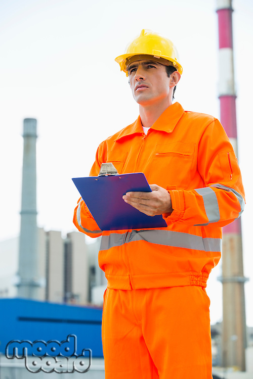 Male architect holding clipboard while standing at site