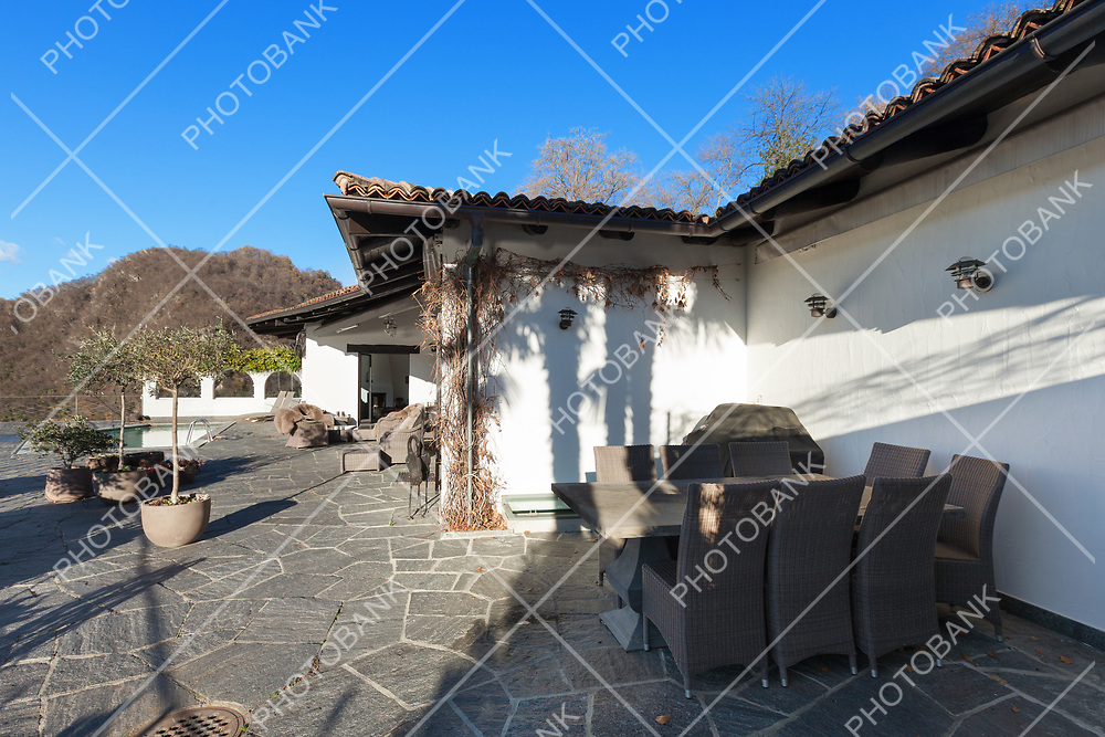 beautiful terrace with pool of a villa, garden furniture