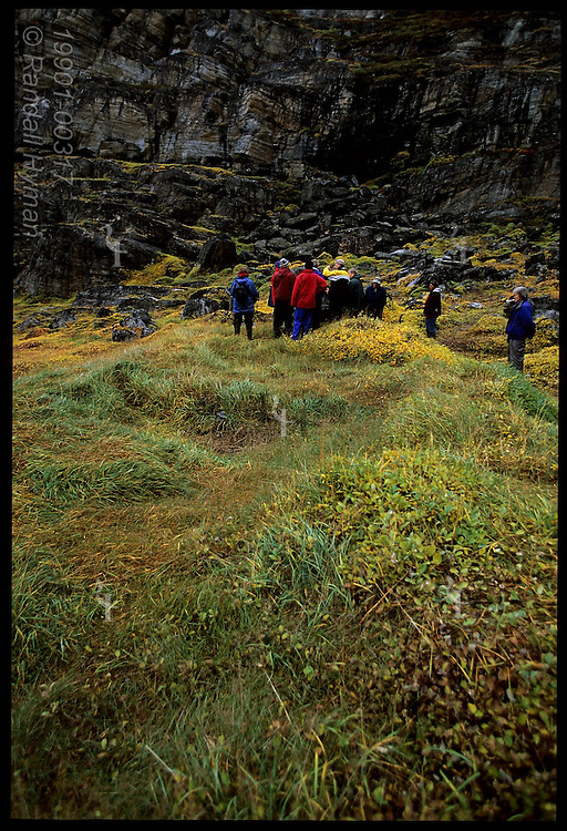 Cruise line passengers gather on grassy slope around the foundations of an ancient stone hut at the Qilakitsoq mummy site; Greenland