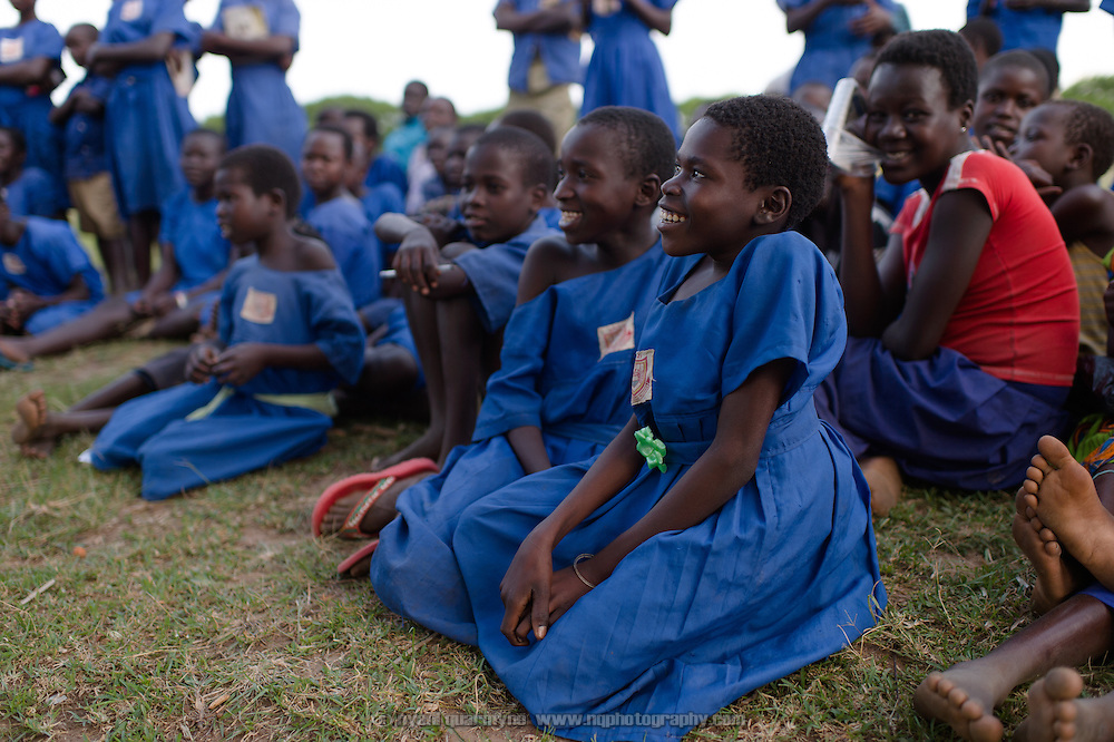 Students watch a drama production dealing with a range of child welfare issues, including child marriages, domestic and sexual abuse, and menstrual hygiene management at Aputiri Primary School in Eastern Uganda on 31 July 2014 as part of a program sponsored by Plan International.