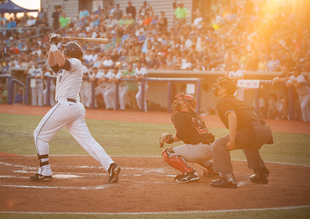 The Hillsboro Hops first baseman, Kevin Cron swings the bat while the Vancouver Canadians catcher, Mike Reeves,  and umpire, Richard Genera, look on in game two of the North West League championships.  Hillsboro won the game to win the 2015 league championship.