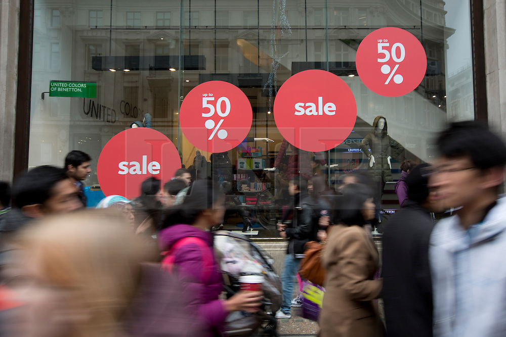 © Licensed to London News Pictures. 26/12/2013. London, UK. Shoppers pass sales signs at the United Colors of Benetton store on Regent Street as they search for bargains during the Boxing Day sales in London today (26/12/2013). Photo credit: Matt Cetti-Roberts/LNP
