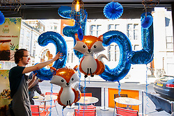 © Licensed to London News Pictures. 03/05/2016. Leicester, UK. Brü Cafe staff putting up Leicester City balloons in their coffee shop as fans celebrate Leicester City winning the 2016 Premier League title the day before in Leicester city centre on Tuesday, 3 May 2016.  Photo credit: Tolga Akmen/LNP