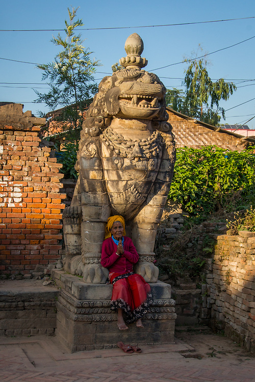 The amount of devotion of people to Hinduism was very apparent during my visit to Kathmandu, Nepal.  This image is of an old woman praying while sitting under a guardian lion sculpture clearly support that.