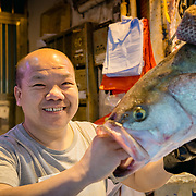 Fishmonger at Bowrington Road wet market, Hong Kong