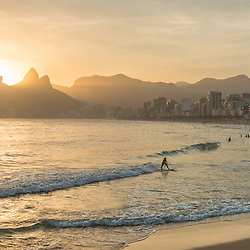 Girl surfing the waves of Ipanema beach at sunset, Rio de Janeiro, Brazil.