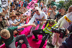 London, UK. 5 July, 2019.  Climate activists from Extinction Rebellion mime being pepper-sprayed by French police during a protest outside the French embassy in solidarity with members of Extinction Rebellion France who were pepper-sprayed at short range by French police after they occupied the Pont de Sully in central Paris to call for more government action and media attention on climate change.