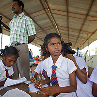 M. Dhanushika, age 11 (looking up) in class in a UNICEF-supplied Temporary Learning Space.<br /> <br /> Sisters M. Dhanushika, age 11 (left) and M. Dilushana, age 9 are from Sri Lanka's Tamil community. They lost their mother in 2006 after she was raped and killed, allegedly by TMVP troops loyal to Colonel Karuna. Their father has subsequently remarried and refuses to be involved in the upbringing of his daughters who live together in a temporary makeshift shelter supplied by UNHCR. The two sisters rely on their aunt and uncle for care. Dhanushika and Dilushana attend Vadamunai Government Tamil Mixed School but often miss classes because they must work collecting reeds which provides them their only source of income. Despite the challenges of their situation, Dhanushika is a particularly conscientious child. As well as taking responsibility for her own necessities, she is committed to her sister's well being. The girls rely on a meal provided by the school every day. Despite the support of neighbours, their present situation is not sustainable and they are likely to be admitted to the care of an orphanage in the near future. <br /> <br /> When fighting between the LTTE and Colombo Government forced the displacement of the local Tamil community in 2007, the Vadamunai Government Tamil Mixed School in Batticaloa District was closed. Since reopening in January 2009, the school has six teaching staff for 88 pupils from Grades 1-9. Before closure,136 pupils studied at the school. Poor road-infrastructure and the remote location of the school means that many staff have to commute for more than three hours. Five classes are held in a UNICEF-supplied Temporary Learning Space. Four other classes are conducted outside, beneath trees. Many of the students suffer with the trauma and stress associated with those living in conflict situations. The staff must deal with these issues as well as the personal difficulties that they themselves suffer living in a conflict environment. To further antagonise an a