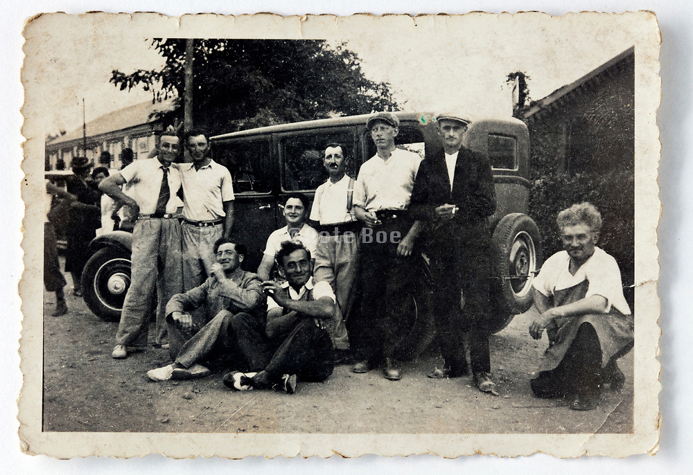 friends posing in front of a sedan car France 1930s