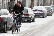 Druk bellend fietst een man in de sneeuw over de Adelaarstraat in Utrecht.<br /> <br /> While on the phone, a man is cycling in the snow at the Adelaarstraat Utrecht.