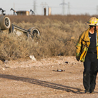 After identifying the body of Rebeca Salinas, 18, her father, right, walks away from the scene of a one-vehicle rollover with Odessa Fire Department captain Bobby Valles Wdnesday, March 1, 2007, on Damascus Road in West Odessa, Texas. A passenger, Rudi Salinas, 5, was taken by CareStar to Medical Center Hospital and was listed in fair condition. A second passenger, Bianca Rojo, 16, had minor injuries.