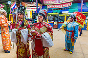 "19 AUGUST 2014 - BANGKOK, THAILAND:  Members of the Lehigh Leng Kaitoung Opera troupe pray in the shrine at the beginning of a performance at Chaomae Thapthim Shrine, a small Chinese shrine in a working class neighborhood of Bangkok. The performance was for Ghost Month. Chinese opera was once very popular in Thailand, where it is called ""Ngiew."" It is usually performed in the Teochew language. Millions of Chinese emigrated to Thailand (then Siam) in the 18th and 19th centuries and brought their culture with them. Recently the popularity of ngiew has faded as people turn to performances of opera on DVD or movies. There are still as many 30 Chinese opera troupes left in Bangkok and its environs. They are especially busy during Chinese New Year and Chinese holiday when they travel from Chinese temple to Chinese temple performing on stages they put up in streets near the temple, sometimes sleeping on hammocks they sling under their stage. Most of the Chinese operas from Bangkok travel to Malaysia for Ghost Month, leaving just a few to perform in Bangkok.             PHOTO BY JACK KURTZ"