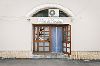 """PISCIOTTA, ITALY - 22 APRIL 2018: The store front of """"Alici di Menaica"""" of Donatella Marinain, both a store selling anchovies products and a processing workshop, is seen here by the harbour in Pisciotta, Italy, on April 22nd 2018.<br /> <br /> Former restaurant owners Donatella Marino and her husband Vittorio Rimbaldo have spent the recent years preparing and selling salted anchovies, called alici di menaica, to a growing market thanks to a boost in visibility from the non-profit Slow Food.  The ancient Menaica technique is named after the nets they use brought by the Greeks wherever they settled in the Mediterranean. Their process epitomizes the concept of slow food, and involves a nightly excursion with the special, loose nets that are built to catch only the larger swimmers. The fresh, red anchovies are immediately cleaned and brined seaside, then placed in terracotta pots in between layers of salt, to rest for three months before they're aged to perfection.While modern law requires them to use PVC containers for preserving, the government recently granted them permission to use up to 10 chestnut wood barrels for salting in the traditional manner. The barrels are """"washed"""" in the sea for 2-3 days before they're packed with anchovies and sea salt and set aside to cure for 90 days. The alici are then sold in round terracotta containers, evoking the traditional vessels that families once used to preserve their personal supply.<br /> <br /> Unlike conventional nets with holes of about one centimeter, the menaica, with holes of about one and half centimeters, lets smaller anchovies easily swim through. The point may be to concentrate on bigger specimens, but the net also prevents overfishing."""