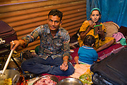 A young woman (right) is applying makeup before performing at one of the regular night dance shows being set up during the yearly Sonepur Mela, Asia's largest cattle market, in Bihar, India. Her husband is cooking while their son is sitting in the small room where they reside for the duration of the Mela.
