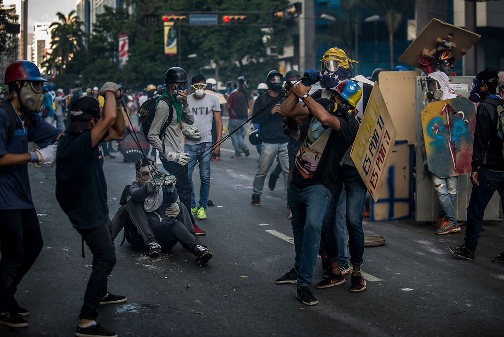 CARACAS, VENEZUELA - MAY 20, 2017:  Anti-government protesters use a giant slingshot to launch glass jars full of paint, and jars full of feces at members of the National Police who responded by heavily tear gassing and firing rubber bullets and buckshot at them. The streets of Caracas and other cities across Venezuela have been filled with tens of thousands of demonstrators for nearly 100 days of massive protests, held since April 1st. Protesters are enraged at the government for becoming an increasingly repressive, authoritarian regime that has delayed elections, used armed government loyalist to threaten dissidents, called for the Constitution to be re-written to favor them, jailed and tortured protesters and members of the political opposition, and whose corruption and failed economic policy has caused the current economic crisis that has led to widespread food and medicine shortages across the country.  Independent local media report nearly 100 people have been killed during protests and protest-related riots and looting.  The government currently only officially reports 75 deaths.  Over 2,000 people have been injured, and over 3,000 protesters have been detained by authorities.  PHOTO: Meridith Kohut