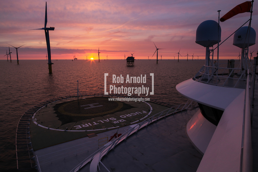 © Rob Arnold.  24/04/2014. North Wales, UK. Sunset aboard the cable trenching vessel, MV Fugro Saltire, on the Gwynt y Môr Offshore Wind Farm off the coast of North Wales. Photo by Rob Arnold
