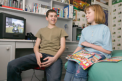 Boy with computer game and girl sitting on the bed reading a magazine in a bedroom,