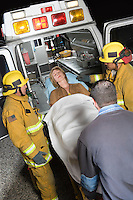 Firefighters and paramedic lifting woman into ambulance