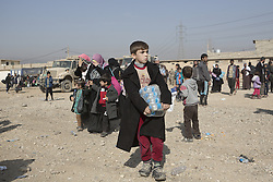 November 11, 2016 - Mosul, Nineveh, Iraq - 11/11/2016. Mosul, Iraq. Iraqi refugees, who have escaped fighting in Mosul, walk with bags in the city's Hay Intisar district on the south east of the city. The district was taken by Iraqi Security Forces (ISF) around a week ago and, despite its proximity to ongoing fighting between ISF and ISIS militants, many residents still live in the settlement...The battle to retake Mosul, which fell June 2014, started on the 16th of October 2016 with Iraqi Security Forces eventually reaching the city on the 1st of November. Since then elements of the Iraq Army and Police have succeeded in pushing into the city and retaking several neighbourhoods allowing civilians living there to be evacuated - though many more remain trapped within Mosul. (Credit Image: © Matt Cetti-Roberts via ZUMA Wire)