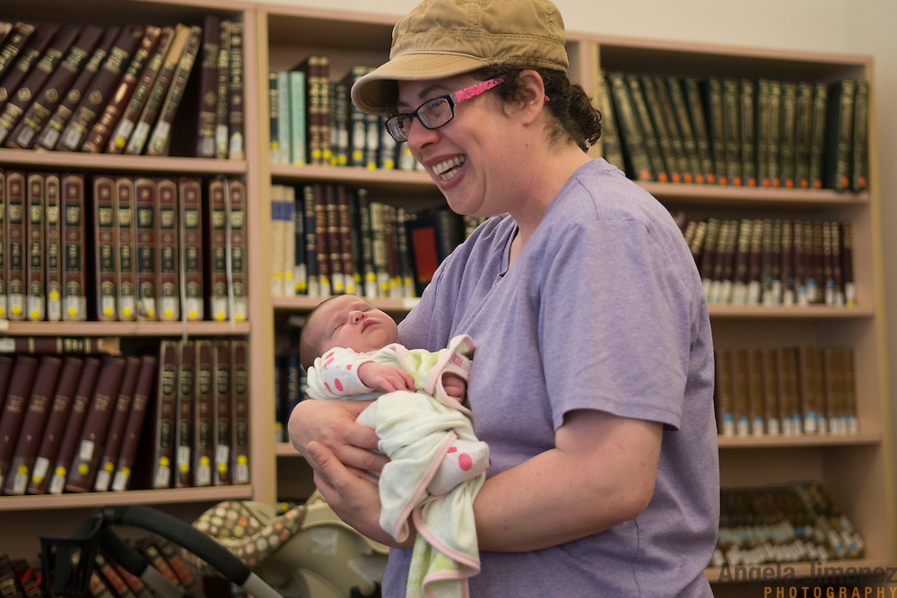 Maharat Talmud Chair Devorah Zlochower holds Susanna &quot;Suzi&quot; Neiss, newborn daughter of Maharat student Rori Picker Neiss, at Drisha. <br /> <br /> The female students of Yeshivat Maharat, &quot;the first institution to train Orthodox women as spiritual leaders and halakhic authorities,&quot; study at the Drisha Institute in New York City in preparation for the school's inaugural graduation on June 16, 2013. <br /> <br /> Three women will be the first to graduate from the four-year school and will be given the title &quot;Maharat&quot;, a Hebrew acronym for &quot;Manhiga Hilkhatit Rukhanit Toranit&quot; which translates to a teacher of Jewish law and spirituality.The school, which currently has 14 students, was founded by Rabbi Avi Weiss. Rabbi Wiess controversially ordained the first female Orthodox Rabba in history, Rabba Sara Hurwitz, who serves as the dean of the school. <br /> <br /> Devorah Zlochower, one of the earliest female Talmudic scholars, was one of the Rabba Hurwitz' teachers when she was a student at Drisha. <br /> <br /> <br /> <br /> <br /> Photo by Angela Jimenez <br /> www.angelajimenezphotography.com