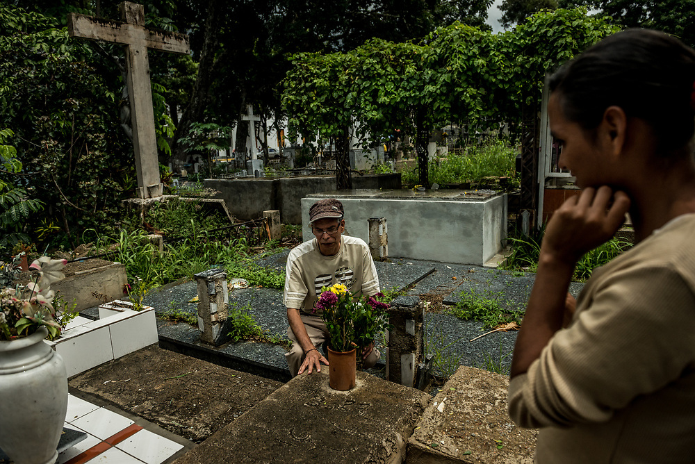 CARACAS, VENEZUELA - JULY 8, 2017: Nerio Parra, 55, and Abigail Torres, 27, visit the graves of  two of their five children who died from severe acute malnutrition.  Their 7-month old daughter, Nerysangely Parra died in September 2016 when the family could not find infant formula for sale despite tirelessly searching. The economic crisis made the family's financial situation so dire, they could only afford to feed their children once a day. The morning Neysangely died, she was sluggish and very thin. Her parents carried her in the rain to the hospital, where she died.  Abigail was so distraught, she broke down and refused to let go of her daughter's body to be taken to the morgue. Hospital security had to forcibly separate the two.  Three months later, on December 1, 2016, their five year old son, Neomar Parra died from severe acute malnutrition and dehydration.  After Neomar died, social services took away the three remaining children and placed them in childrens' homes.  Each Saturday and Thursday, Abigail and Nerio visit their children in foster care, then go to the cemetery to visit the graves of their two deceased children.  As the economic crisis worsens in Venezuela, more and more working class families are struggling to feed their families. Hundreds of children have died in the past year from severe acute malnutrition - a cause of death seldom seen in Venezuela three years ago, before the crisis. PHOTO: Meridith Kohut for The New York Times