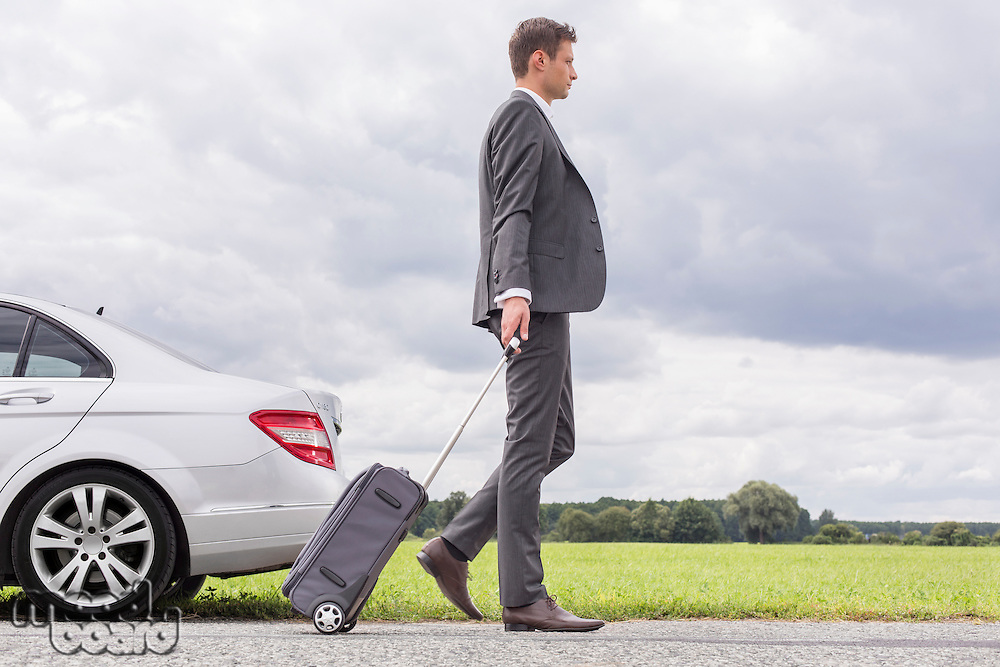 Full length side view of young businessman with luggage leaving broken down car at countryside