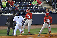 Georgia third base coach Allen Osborne (20) tells Georgia's Zach Cone (12) to head for home to score as the ball gets past Ole MIss' Preston Overbey (1) in a college baseball action at Oxford-University Stadium in Oxford, Miss. on Friday, April 8, 2011. Georgia won 9-8.
