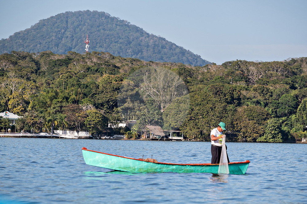 A fisherman prepares to cast a net into Lake Catemaco in Catemaco, Veracruz, Mexico. The tropical freshwater lake at the center of the Sierra de Los Tuxtlas, is a popular tourist destination and known for free ranging monkeys, the rainforest backdrop and Mexican witches known as Brujos.