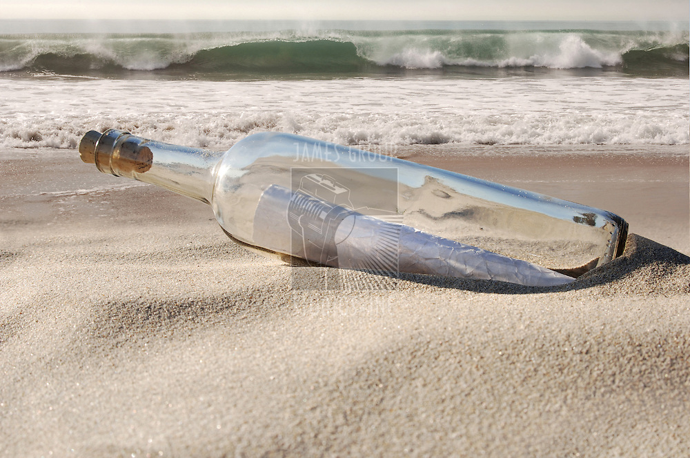mystery message in a clear glass bottle emerging from the sand of an ocean beach