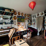 May 10, 2012 - Brooklyn, NY : The living room in musician and composer Michael Arenella's apartment on Douglas Street in Brooklyn is adorned with a collection of hats, musical instruments, and a painting by his father, Joe Arenella. CREDIT : Karsten Moran for The New York Times