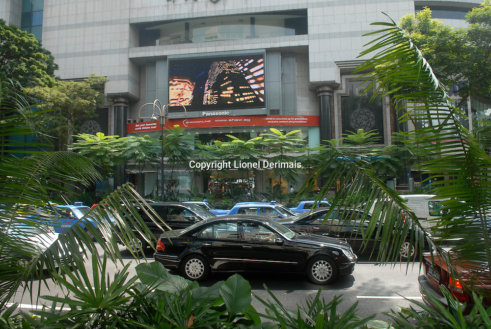 A black Mercedes-Benz on Orchard road at the corner of Scotts and Paterson.