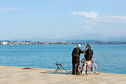 SANTANDER, SPAIN - April 18 2018 - Fishermen talk along Santander seafront with view looking out to Somo beach and waterfront, Cantabria, Northern Spain, Europe.