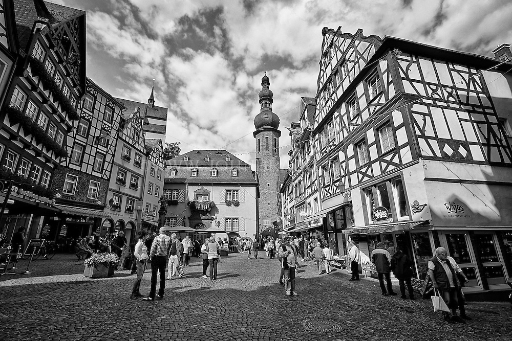 Black and white view of the Cochem Town Square, Bustling Market, Shoppers, and Tower, Cochem, Germany.