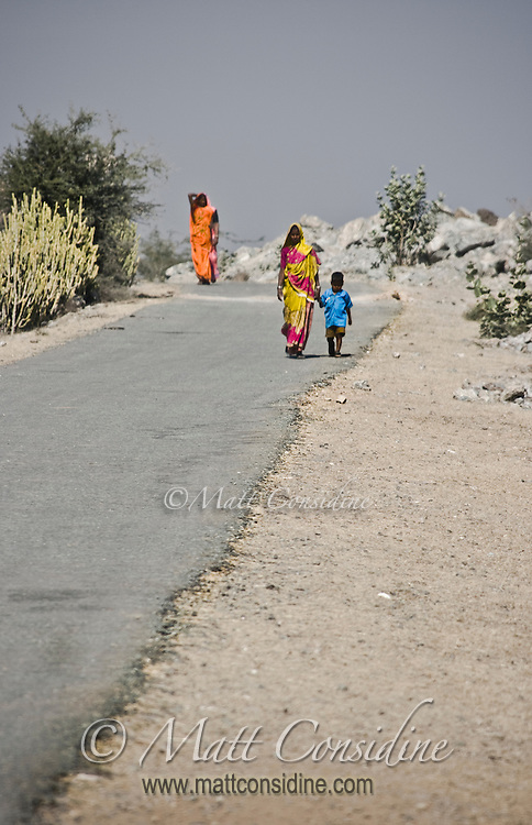 Colorful saris contrast with the stark, dry landscape of rural Rajasthan.<br /> (Photo by Matt Considine - Images of Asia Collection)