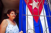 25 JULY 2002 - HAVANA, HAVANA, CUBA: A woman in her doorway with a Cuban flag in the historic section of Havana, Cuba, July 25, 2002..PHOTO BY JACK KURTZ