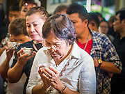 12 OCTOBER 2104 - BANG BUA THONG, NONTHABURI, THAILAND: People line up and wait to pay respects at the funeral rites for Apiwan Wiriyachai at Wat Bang Phai in Bang Bua Thong, a Bangkok suburb, Sunday. Apiwan was a prominent Red Shirt leader, member of the Pheu Thai Party of former Prime Minister Yingluck Shinawatra, and a member of the Thai parliament. The military government that deposed the elected government in May, 2014, charged Apiwan with Lese Majeste for allegedly insulting the Thai Monarchy. Rather than face the charges, Apiwan fled Thailand to the Philippines. He died of a lung infection in the Philippines on Oct. 6. The military government gave his family permission to bring him back to Thailand for the funeral. He will be cremated later in October. The first day of the funeral rites Sunday drew tens of thousands of Red Shirts and their supporters, in the first Red Shirt gathering since the coup.    PHOTO BY JACK KURTZ