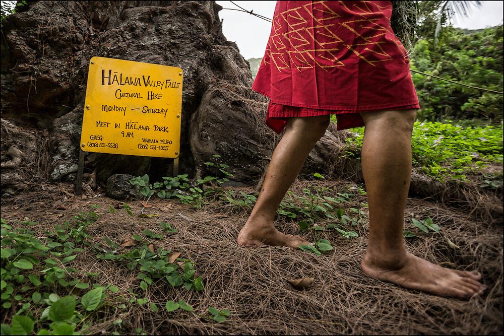 Anakala Pilipo Solatorio walks past his homemade sign for his ohana's daily cultural hike in Halawa Valley on Molokai. ©PF Bentley