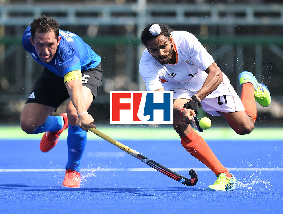 Argentina's Pedro Ibarra (L) and India's Akashdeep Singh stretche for the ball during the men's field hockey Argentina vs India match of the Rio 2016 Olympics Games at the Olympic Hockey Centre in Rio de Janeiro on August, 9 2016. / AFP / MANAN VATSYAYANA        (Photo credit should read MANAN VATSYAYANA/AFP/Getty Images)
