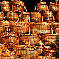 Wicker Baskets on Display at Outdoor Market in Eger, Hungary<br /> Similar to most cities, Eger has a mall: The Agria Park Shopping Centre. But when traveling to a foreign country, why focus on brand merchandise or T-shirts, shot glasses and trinkets? Visit where the residents' shop. Széchenyi is the main, pedestrian-only shopping street. Best of all are the outdoor markets. They speak volumes about the local cuisine, agriculture, economy, social interaction and pace of life. You will find some simple yet elegantly crafted items such as these wicker baskets on display at an outdoor market. They beg to be loaded up with the seasonal fruit and vegetables from the nearby produce section.