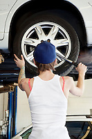 Back view of young female mechanic working on lifted car's tire in automobile repair shop